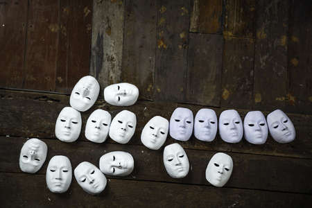 multiple personality: Abstract white masks on wooden background Stock Photo