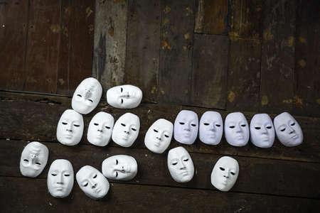 personalit�: Astratto maschere bianche su fondo in legno Archivio Fotografico