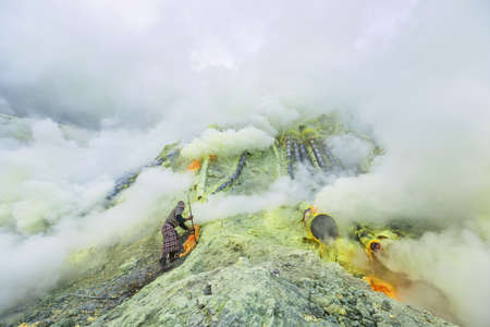 Miners dig sulphur in fumes of toxic volcanic gas at the sulphur mines in the crater of the active volcano of Kawah Ijen, East Java, Indonesia. Reklamní fotografie