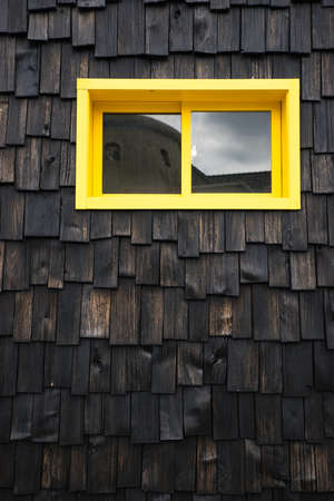 Yellow window on wooden texture background