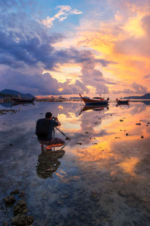 Photographer is taking a picture of sunrise with traditional  boats at Rawai Beach, Phuket, Thailand.