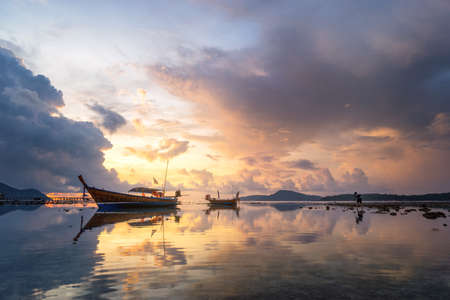 A photographer take a shot of fishing Boat with the sunrise in the sea with reflection and cloud , Phuket ,Thailand, Scenery of beach during twilight  Stock Photo