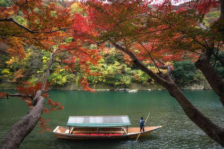 Boatman punting the boat at river. Arashiyama in autumn season along the river in Kyoto, Japan. 写真素材