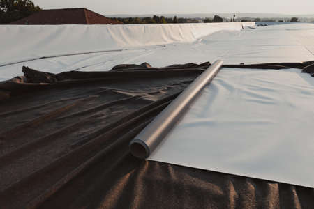Roofing PVC membrane in rolls placed on the roof of the site Foto de archivo