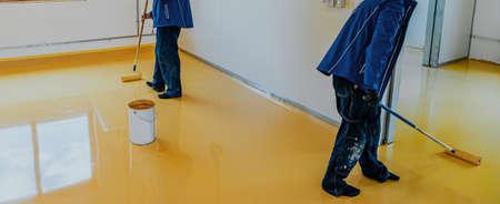 Worker, coating floor with self-leveling epoxy resin in industrial workshop. Foto de archivo