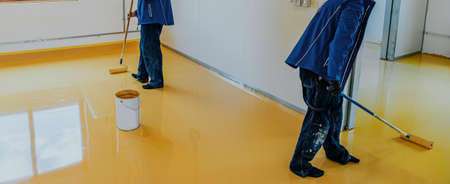 Worker, coating floor with self-leveling epoxy resin in industrial workshop.