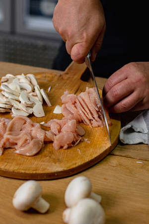 Chef slices chicken breast on a wooden chopper with mushrooms next to it.