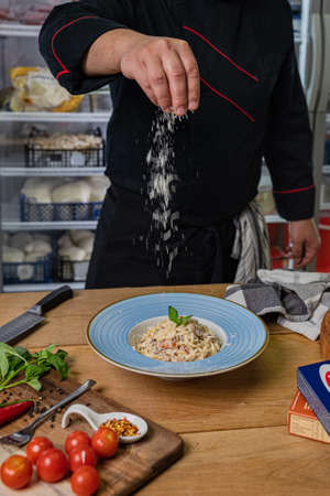 The chef puts pasta from the pan and do the plating. Zdjęcie Seryjne
