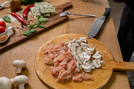Slices of fresh chicken breast on wooden chopper with mushrooms next to it and spices