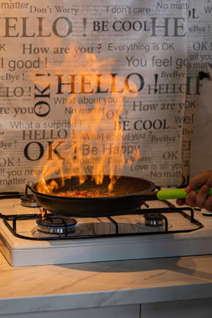 Chef cooking with flame in a frying pan on a kitchen stove