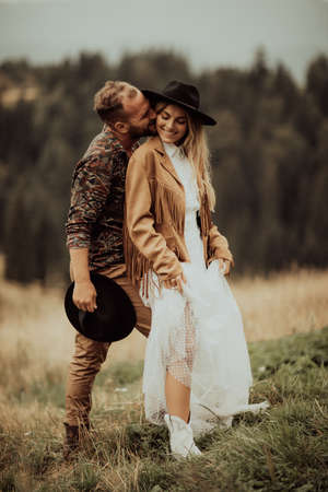 Beautiful stylish  couple hugging and laughing at their intimate wedding. Autumn season