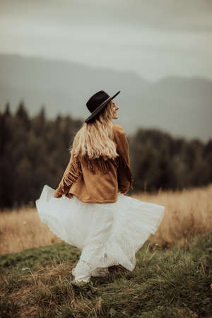 Young bride dressed in boho style with boots and hat, enjoying the sun in a breathtaking mountain landscape.