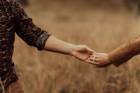 Beautiful stylish  couple walks holding hands in a Carpathian mountain landscape.