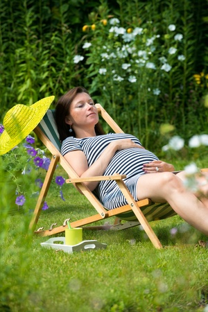 Pregnant woman relaxing in the garden photo