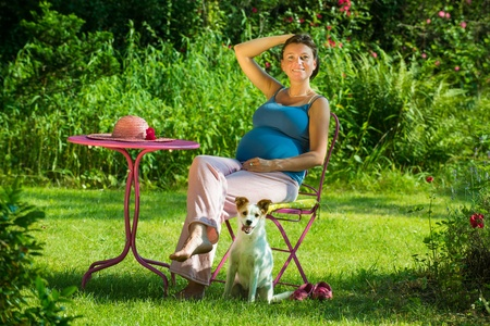 Pregnant woman sitting in a garden with dog photo