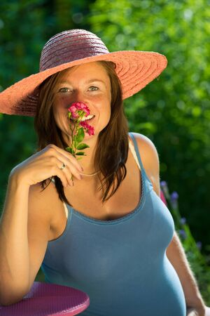 Pregnant woman smells on a rose photo
