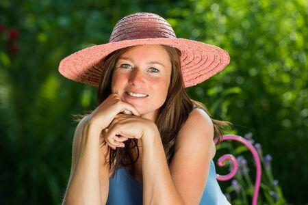 mensch: Junge Frau mit Strohhut lächelt in die Kamera