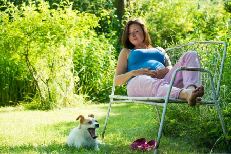 Pregnant woman sitting in a garden