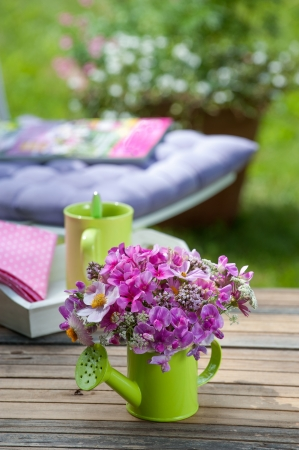 Colorful flowers in a watering can photo