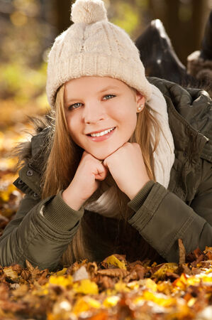 Girl lying in colorful autumn leaves photo