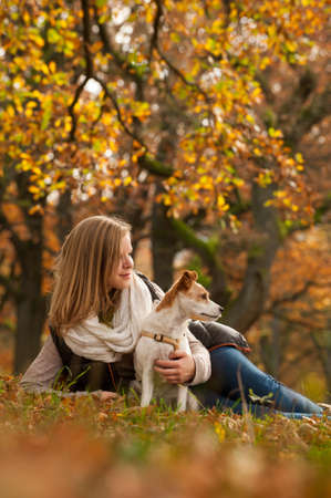 Girl with dog in autumn landscape photo