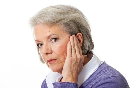 dolor de o�do: Mujer madura con el ruido en el o�do Foto de archivo