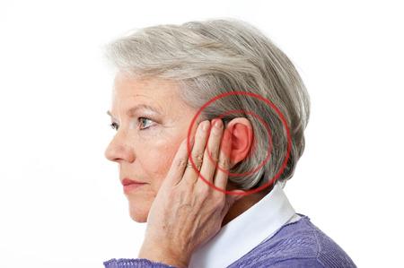 dolor de oido: Mujer madura con el ruido en el o�do Foto de archivo