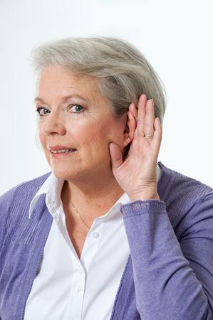 personas escuchando: Mujer madura que sostiene la mano al o�do Foto de archivo