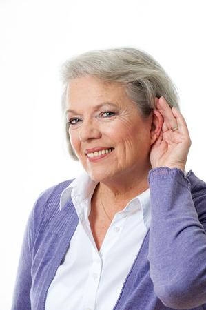 dolor de oido: Mujer madura que sostiene la mano al o�do Foto de archivo