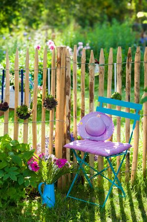 picket green: Idyllic garden with table and chair Stock Photo