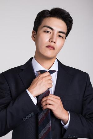 Studio portrait of a confident businessman posing against a gray background Stock Photo