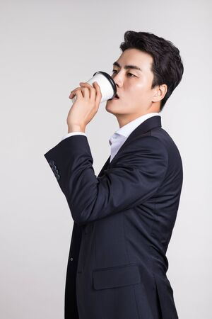 Studio portrait of an Asian business man posing with a disposable coffee cup