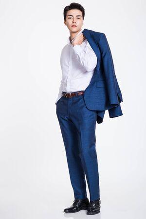 Studio portrait of a confident businessman posing against a gray background Foto de archivo