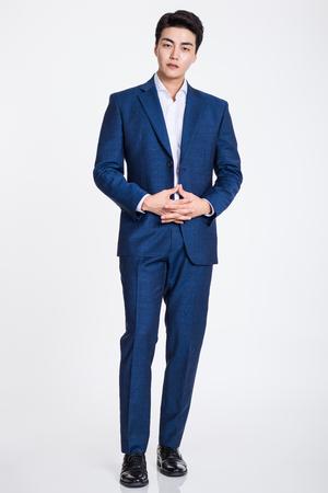 Studio portrait of a confident businessman posing against a gray background 写真素材