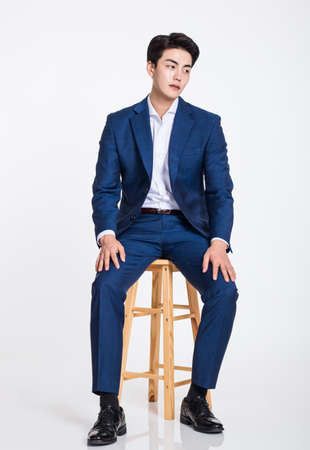Studio portrait of a young Asian business man sitting in a chair