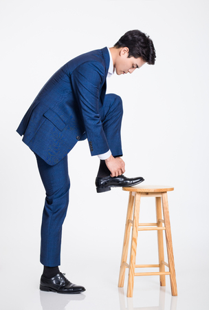 Studio shot of a young Asian businessman wearing a shoelace raising his foot on a chair