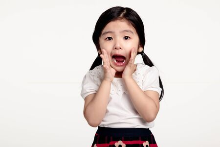 romp: A studio portrait of an asian girl with a surprised look at something Stock Photo