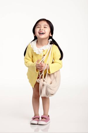 voguish: Studio portrait of a happy asian girl holding a bag