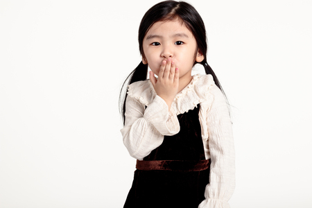 Studio portrait of Asian girl with hands on mouth
