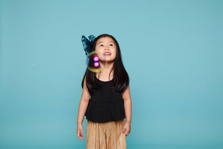 voguish: Studio portrait of asian girl with soap bubbles in front of blue background