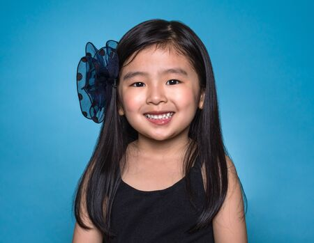 voguish: Studio portrait of Asian girl with happy look in front of blue background