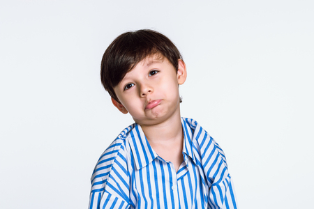 Studio portrait of a boy who is disappointed because he does not get what he wants Stock Photo