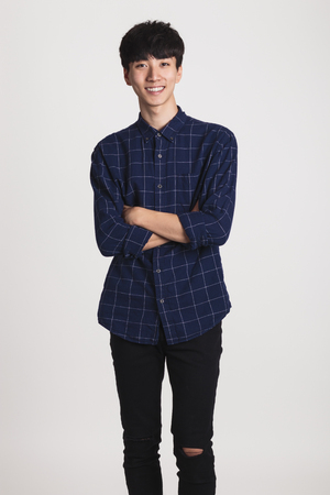 Studio portrait of Asian young man with happy smile and looking at camera 版權商用圖片