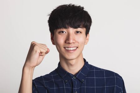 Studio portrait of Asian youth with confident pose and smile