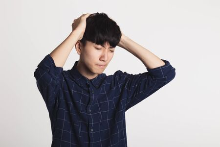A studio portrait of a painful Asian youth, holding his head in his hand