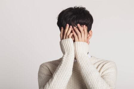 Cover your face with your hands, Studio portrait of a sad Asian young man Stok Fotoğraf