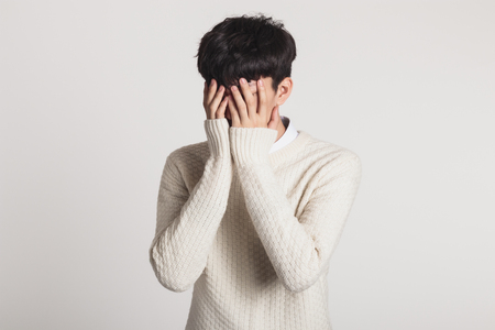 Cover your face with your hands, Studio portrait of a sad Asian young man Stock Photo