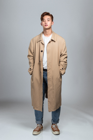A studio portrait of an Asian Asian man posing in a coat
