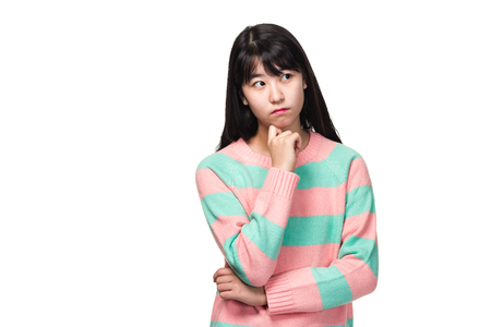 Studio portrait of teenage East Asian woman worried and thinking