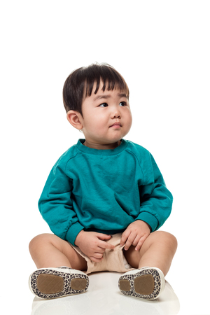 Studio portrait of an East Asian young child with a serious look on a white background